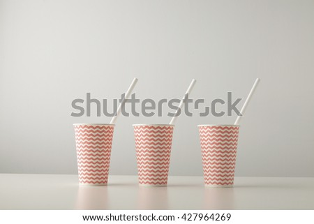 Retail set of three paper cups decorated with red line pattern and with white drinking straw inside isolated on white table Place for your text above - stock photo
