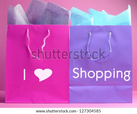 Retail therapy, I love shopping, concept with colorful shopping bags against a feminine pink background, with I Heart Shopping message. - stock photo