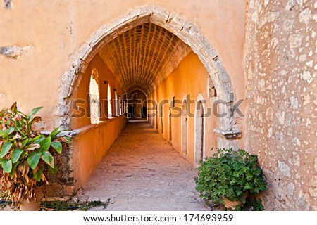 RETHYMNO, GREECE - OCTOBER 15, 2013: The courtyard of Arkadi Monastery is surrounded by shady galleries, where visitors may walk and enjoy the views of garden and basilika, on October 15 in Rethymno. - stock photo