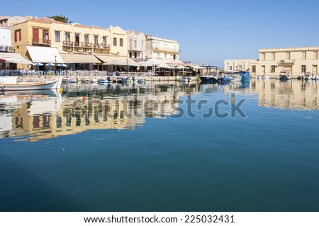 RETHYMNO, GREECE - SEPTEMBER 13. Taverns and Fishing boats in the harbor of Rethymno on September 13, 2014. Rethymno is nice city with a wonderful old city part and venetian port located on Crete - stock photo