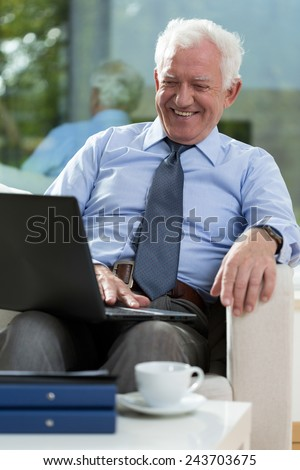 Retired businessman sitting on the chair and using laptop - stock photo
