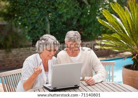 Retired couple buying something on internet - stock photo