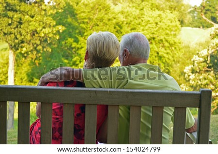 retired couple embracing one another - stock photo