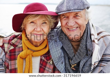 Retired couple in warm clothes looking at camera - stock photo