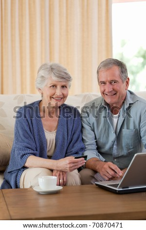 Retired couple looking at their laptop at home