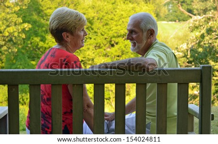 retired couple sitting on a bench - stock photo