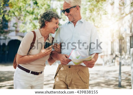 Retired couple walking around the town with a map. Smiling mature man and woman roaming around the city. - stock photo