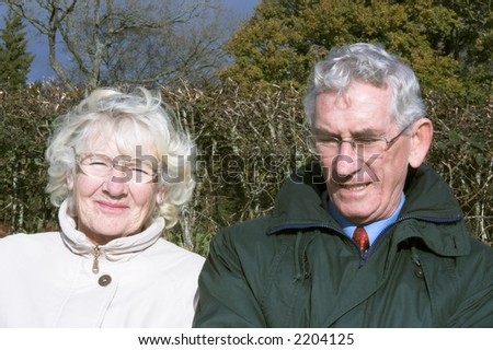 Retired couple, white and grey haired outside on a sunny autumn / fall / winter day enjoying the sunshine and the view