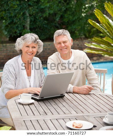 Retired couple working on their laptop - stock photo