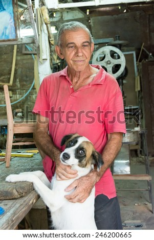 Retired Cuban carpenter,nowadays self employed at home with his own homemade carpentry taking a break and petting his dog. - stock photo