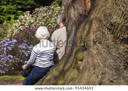 Retired elderly couple in the park - stock photo