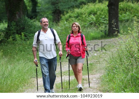 Retired elderly people hiking in forest pathway - stock photo