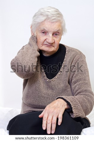 Retired elderly woman sitting on the bed - stock photo