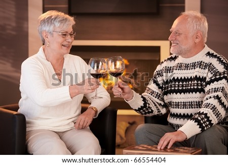 Retired husband and wife drinking red wine together in cosy living room, in front of fireplace, looking happy, smiling.? - stock photo