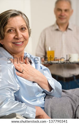 Retired husband bringing breakfast to bed to her ill wife - stock photo