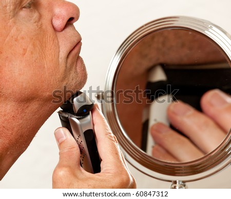 Retired male shaving with electric razor in front of magnifying mirror - stock photo