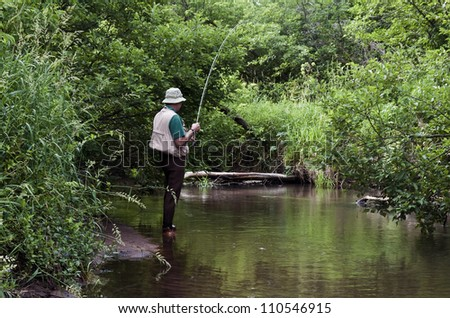 retired man fishing a small stream with a fly rod - stock photo