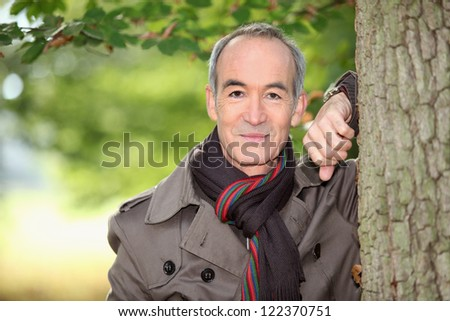 Retired man having a walk through the woods - stock photo