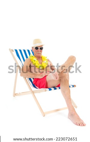 Retired man on vacation sitting in beach chair drinking beer - stock photo