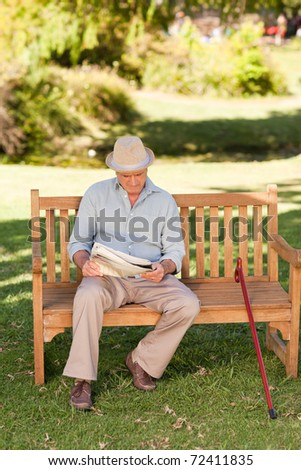 Retired man reading his newspaper on the bench