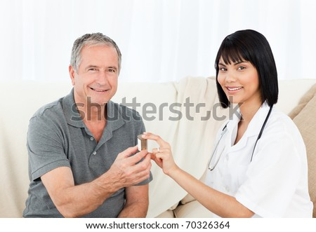 Retired man with his nurse looking at the camera at home