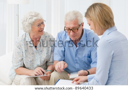 Retired old couple planning their investments with a financial consultant - stock photo