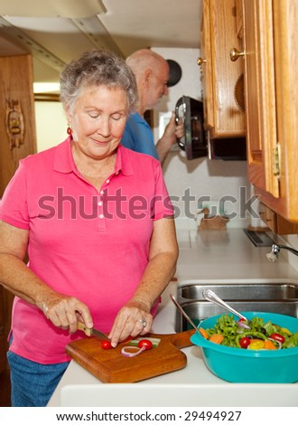 Retired senior couple cooking together in the kitchen of their motor home. - stock photo