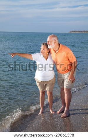Retired senior couple on vacations taking in the sights at the beach. - stock photo