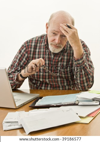Retired senior male at his desk worrying how he will pay the bills. - stock photo