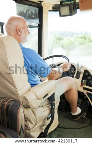 Retired senior man driving his motor home on vacation. - stock photo