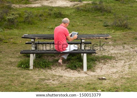 Retired senior man resting and using his tablet at table in park outdoors in grass dune landscape.