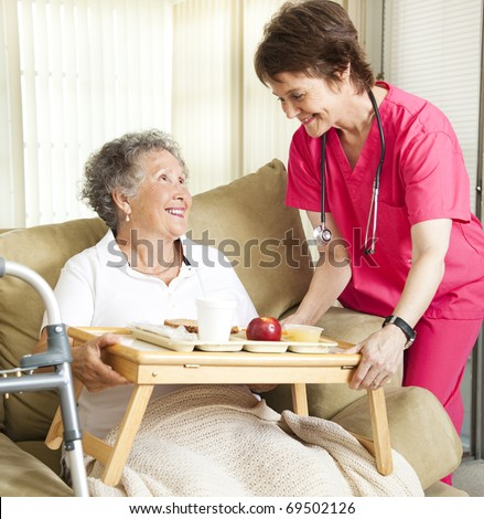 Retired senior woman in nursing home gets lunch from a caring nurse. - stock photo