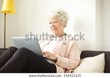Retired senior woman sitting at home using her laptop - stock photo