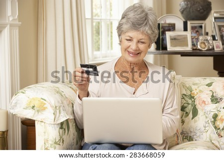 Retired Senior Woman Sitting On Sofa At Home Using Laptop To Make Online Purchase - stock photo