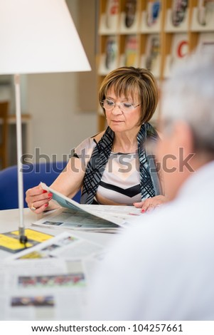 Retired seniors, old woman reading paper with husband in recreation center. Dolly shot - stock photo