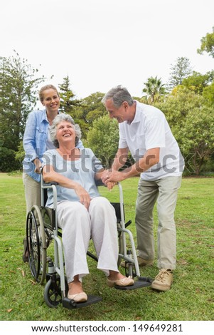 Retired woman in wheelchair with husband and daughter laughing in the park