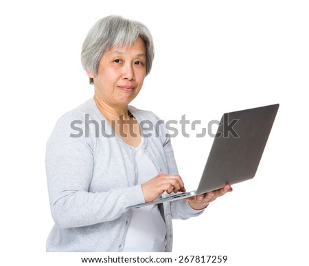 Retired woman learn to use laptop - stock photo