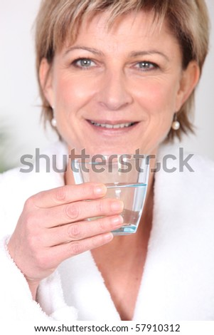 Retired woman with glass of milk in hand - stock photo