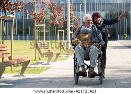 Retiree sitting in a wheelchair and his granddaughter - stock photo