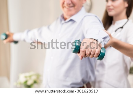 Retiree training with dumbbells assisted by young physiotherapist - stock photo