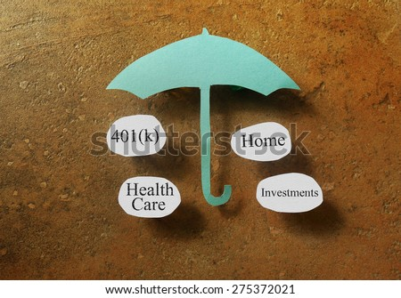 Retirement and investing terms under a paper umbrella - retirement planning concept                                - stock photo