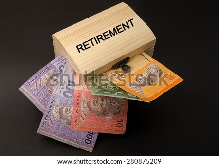 Retirement label above the wooden box containing the money black background - stock photo