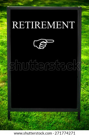 RETIREMENT message and hand pointing to the right on sidewalk blackboard sign against green grass background. Copy Space available. Concept image - stock photo