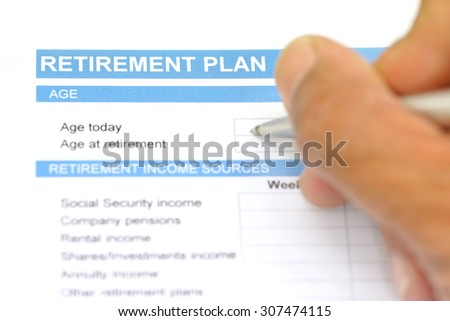 retirement plan document with pen and human hand