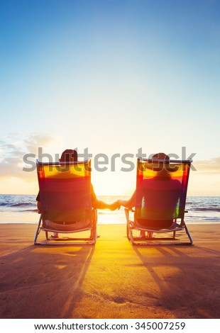 Retirement Vacation Concept, Happy Mature Retired Couple Enjoying Beautiful Sunset at the Beach - stock photo