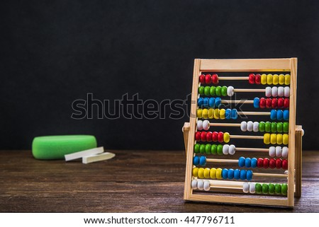 retro abacus in classroom agains black empty chalkboard - stock photo