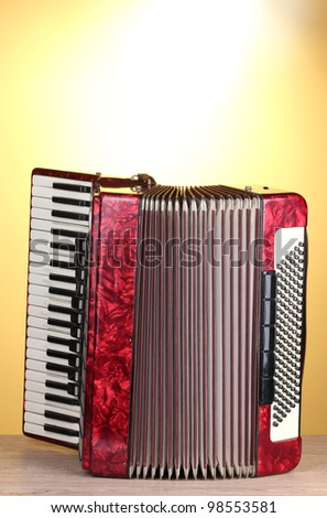 Retro accordion on wooden table on yellow background