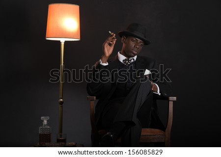 Retro african american gangster man wearing striped suit and tie and black hat. Sitting in a chair in living room. Smoking cigar. - stock photo
