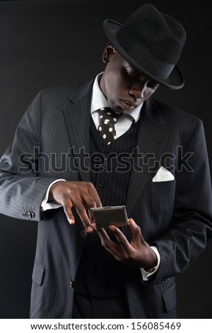 Retro african american gangster man wearing striped suit and tie and black hat. Taking cigarette out of silver box. Studio shot.