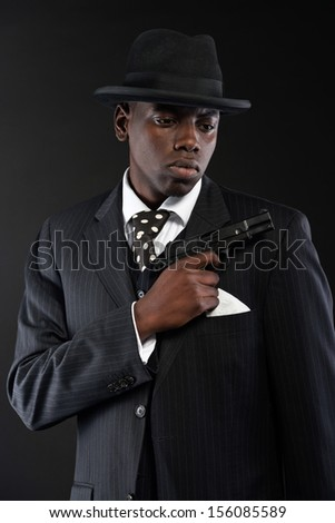 Retro african american mafia man wearing striped suit and tie and black hat. Holding a gun. Studio shot.